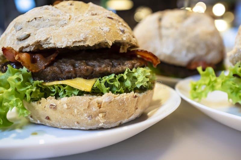 Hamburguesa apetitosa con carne de vaca, queso, lechuga y tocino frito en una placa, entre otros cheeseburgers foto de archivo