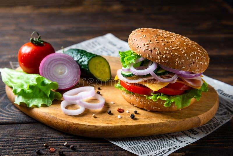 Hamburguesa apetitosa con el jamón, el tomate, los pepinos, el queso y la lechuga, cierre para arriba imagen de archivo libre de regalías