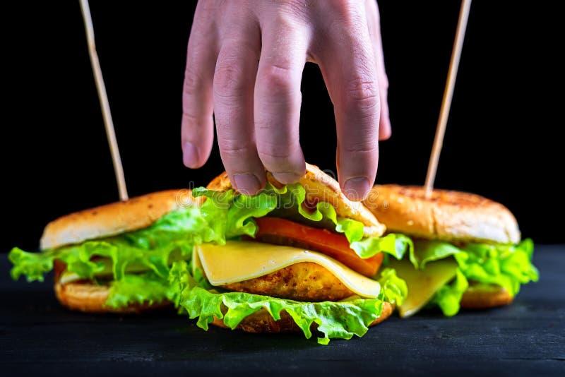 Hamburguesa apetitosa y fresca en una tabla negra de madera, haciendo publicidad de la bandera foto de archivo