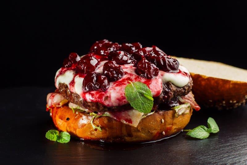 Hamburguesa, bocadillo de la hamburguesa con la chuleta de la carne picadita, brie del queso, camembert, cereza de la baya fotografía de archivo libre de regalías