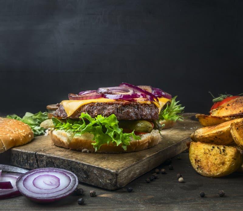 Hamburguesa casera jugosa apetitosa con la carne de vaca, la ensalada, los pepinos conservados en vinagre, el queso y la cebolla, imagen de archivo