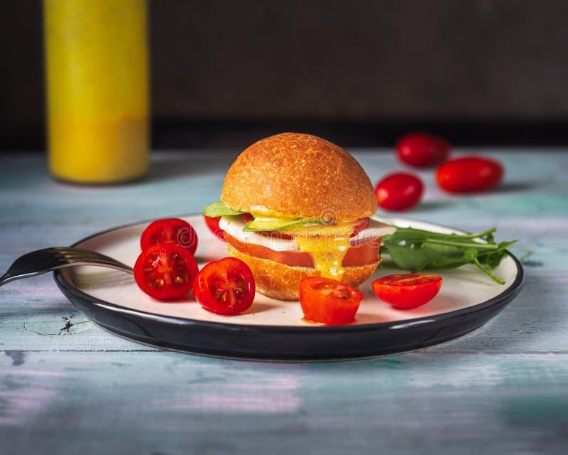 Hamburguesa con el jamón y queso, tomates y salsa en una placa de cerámica redonda, tiro de la gama cercana, arugula fresco y cer fotografía de archivo