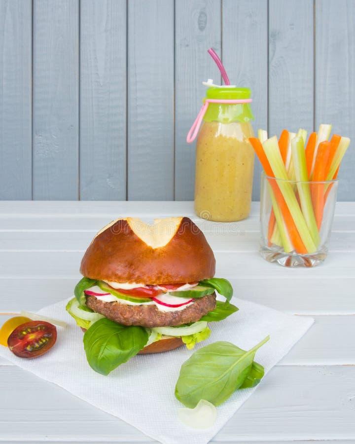 Hamburguesa con la chuleta con las verduras, y smoothie verde con los palillos del apio y zanahorias encendido y fondo de madera  foto de archivo