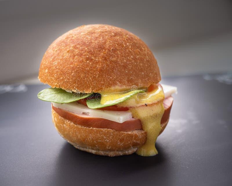 Hamburguesa con la salchicha, el queso y el tomate, arugula, rematado con la salsa imagen de archivo libre de regalías
