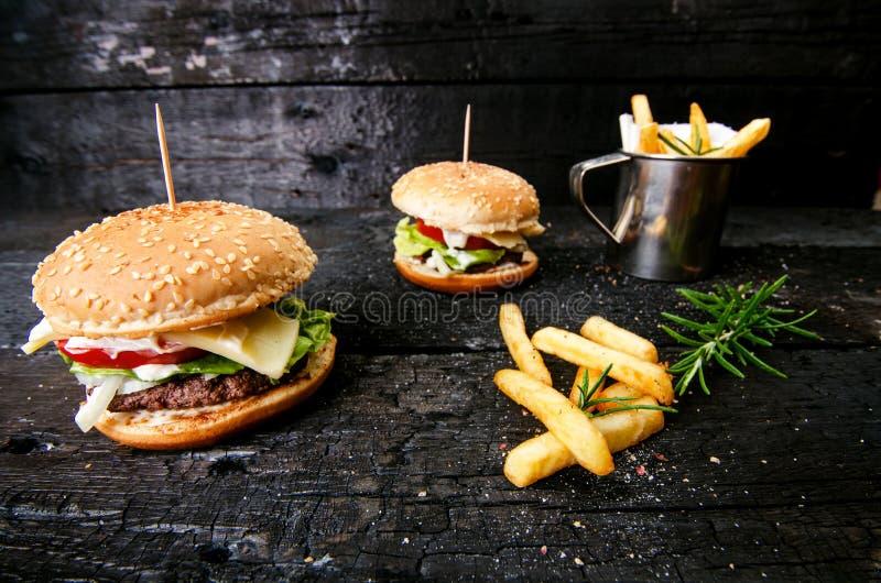 Hamburguesa con las patatas fritas, cerveza en una tabla de madera quemada, negra Comida de alimentos de preparación rápida La ha foto de archivo