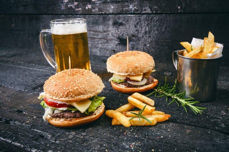 Hamburguesa con las patatas fritas, cerveza en una tabla de madera quemada, negra Comida de alimentos de preparación rápida La ha fotografía de archivo libre de regalías