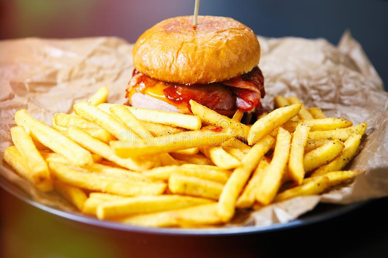 Hamburguesa con las patatas fritas de oro en la placa foto de archivo libre de regalías