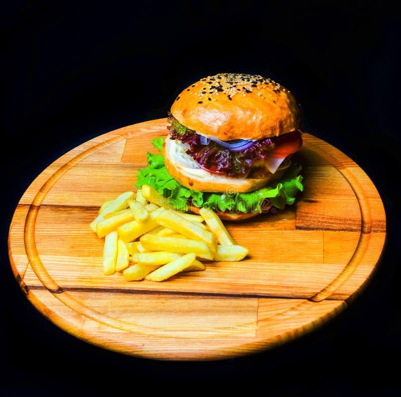 Hamburguesa con las patatas fritas en un tablero de madera Alimentos de preparación rápida foto de archivo