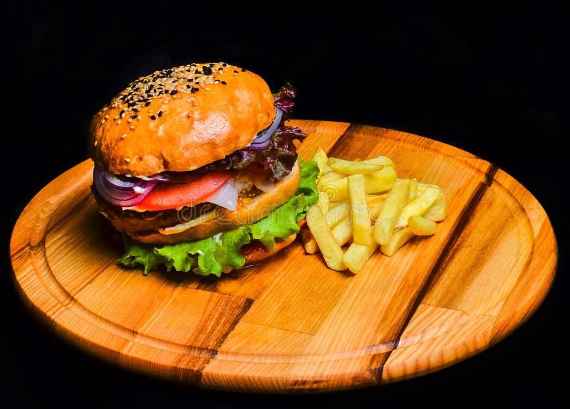 Hamburguesa con las patatas fritas en un tablero de madera Alimentos de preparación rápida imagenes de archivo