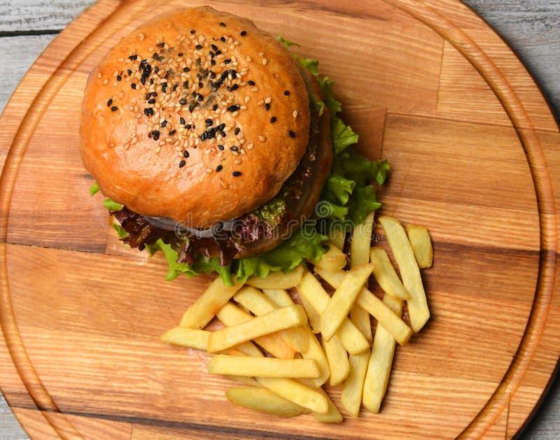 Hamburguesa con las patatas fritas en un tablero de madera Visión superior Alimentos de preparación rápida foto de archivo