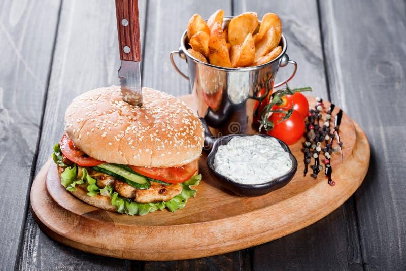 Hamburguesa con las verduras frescas, el queso, la salsa y las fritadas en tabla de cortar en fondo de madera oscuro Hamburguesa  imágenes de archivo libres de regalías