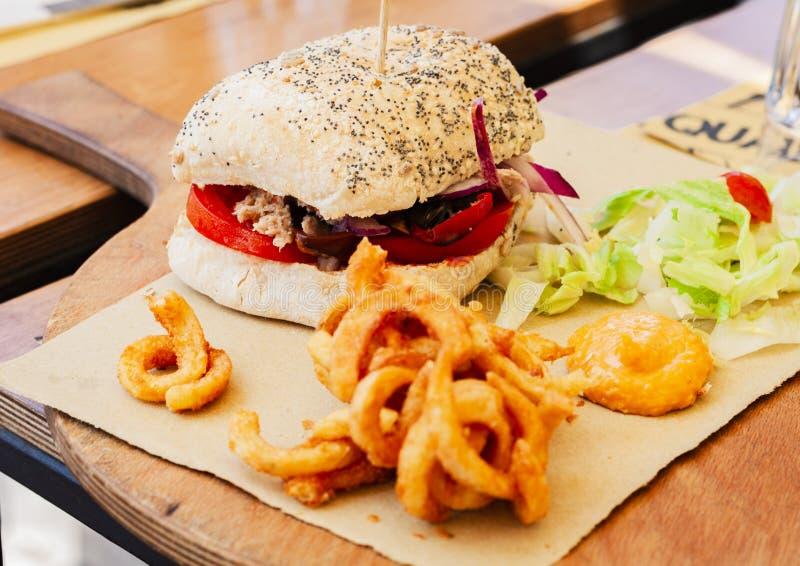 Hamburguesa con los pescados de atún, la ensalada y calamary frita en el restaurante de Syracuse, Sicilia foto de archivo libre de regalías
