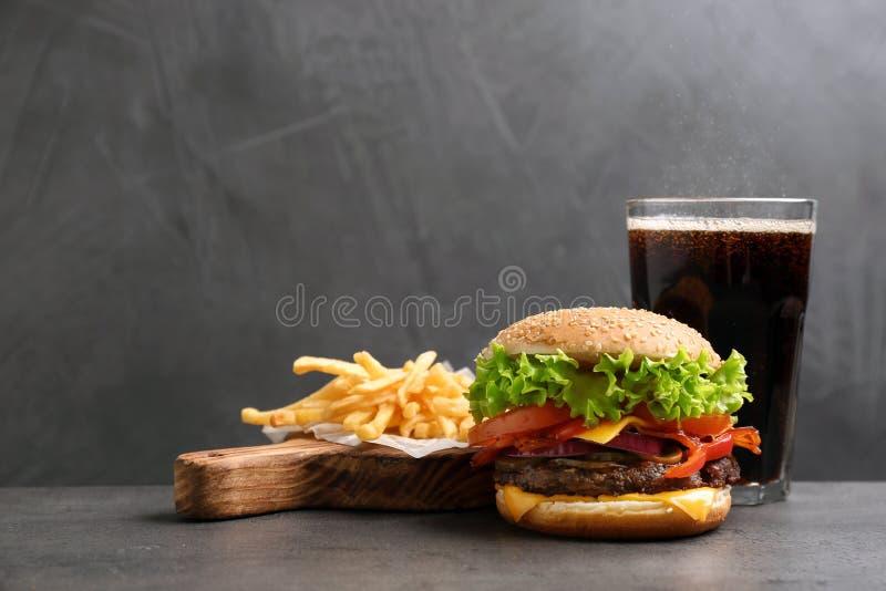 Hamburguesa con tocino, la bebida de la soda y las patatas fritas en la tabla contra fondo gris fotografía de archivo libre de regalías