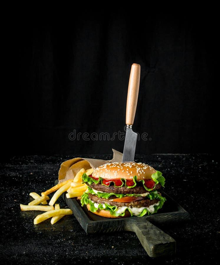 Hamburguesa con un cuchillo y las fritadas fotografía de archivo