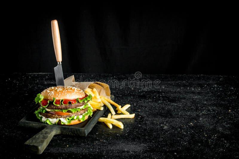 Hamburguesa con un cuchillo y las fritadas imágenes de archivo libres de regalías