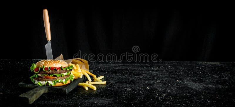 Hamburguesa con un cuchillo y las fritadas foto de archivo libre de regalías