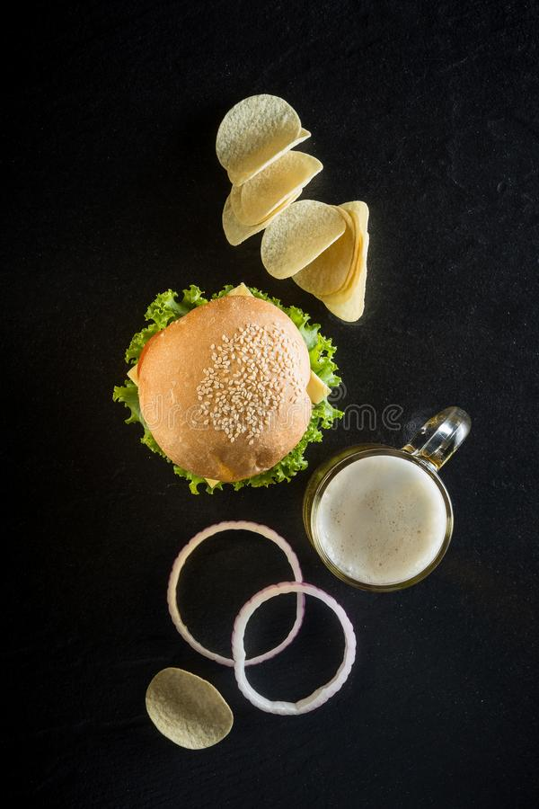 Hamburguesa con una taza de cerveza fría, de salsa de tomate y de microprocesadores curruscantes en d fotografía de archivo