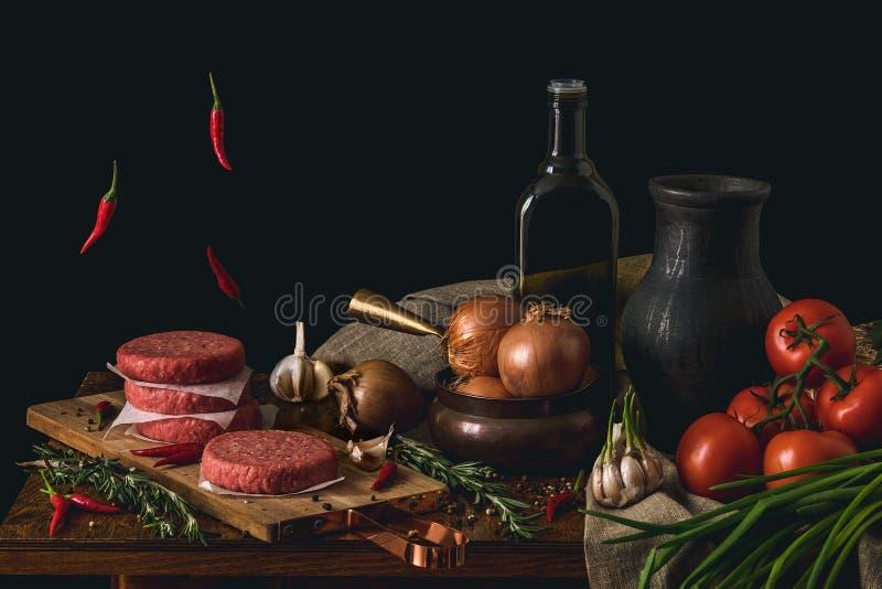 Hamburguesa cruda de la carne de vaca, barbacoa tradicional, aún vida con las verduras y carne foto de archivo libre de regalías