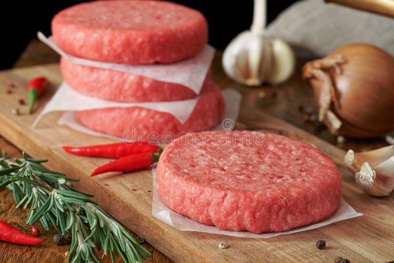Hamburguesa cruda de la carne de vaca, barbacoa tradicional, a?n vida con las verduras y carne fotografía de archivo libre de regalías