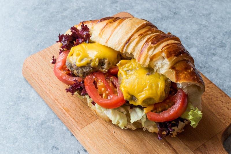 Hamburguesa del cruasán con las albóndigas, el queso cheddar y los tomates foto de archivo