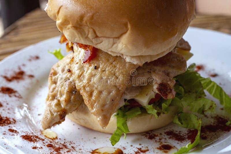 Hamburguesa del pollo con la ensalada en la placa blanca, primer de los snacks Foto del menú del restaurante o del restaurante foto de archivo libre de regalías