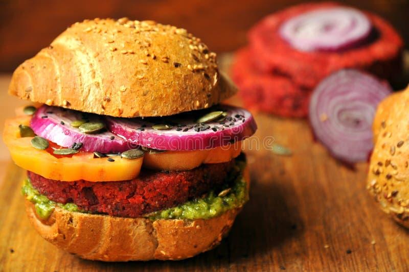 Hamburguesa del vegano con las habas y la remolacha roja en un fondo de madera imagen de archivo