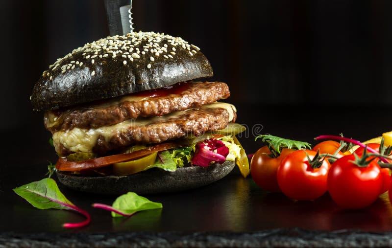Hamburguesa doble negra hecha de la carne de vaca, con pimienta del jalapeno imagenes de archivo