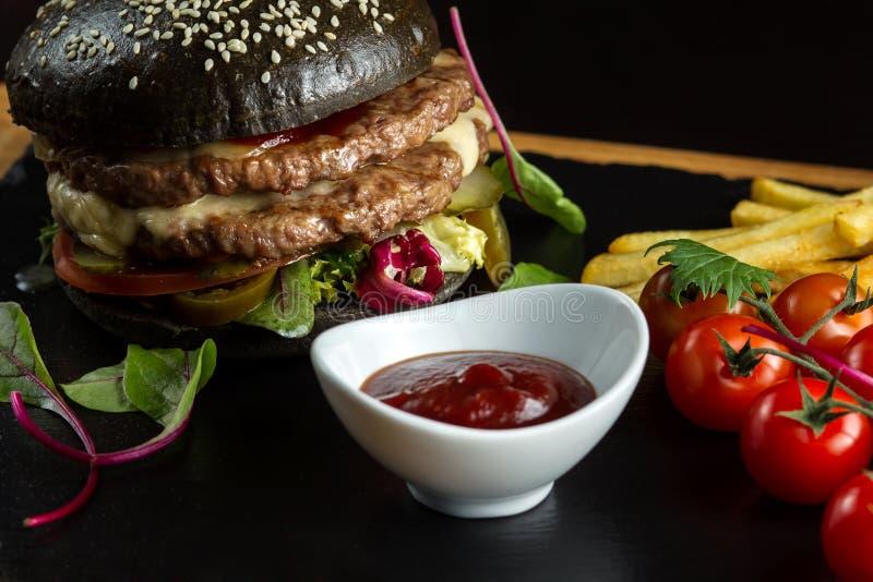 Hamburguesa doble negra hecha de la carne de vaca, con pimienta del jalapeno Salsa de tomate en una salsa blanca foto de archivo