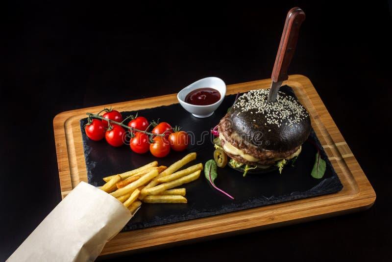 Hamburguesa doble negra hecha de la carne de vaca con pimienta, queso y vegetables-5 del jalapeno imagenes de archivo