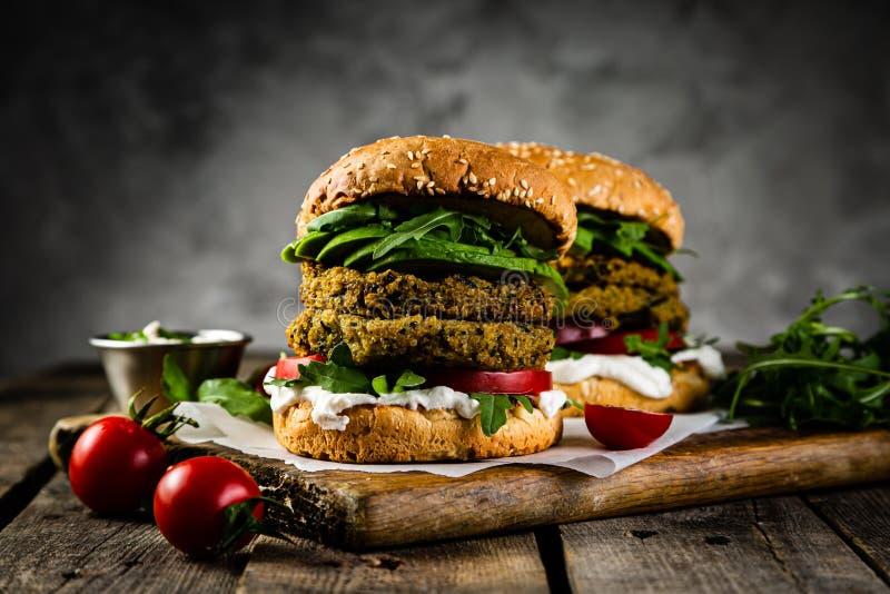 Hamburguesa e ingredientes del calabacín del vegano en fondo de madera rústico foto de archivo libre de regalías