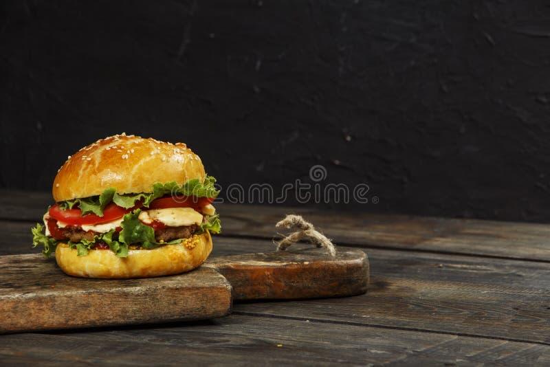 Hamburguesa en un tablero de madera contra un fondo oscuro con el espacio de la copia Hamburguesa con la salsa y las verduras fre imágenes de archivo libres de regalías