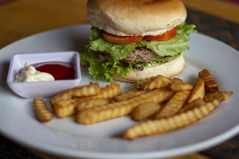 Hamburguesa fresca con la chuleta, las patatas fritas, la salsa de tomate y la mayonesa de la carne Hamburguesa americana de la c foto de archivo libre de regalías