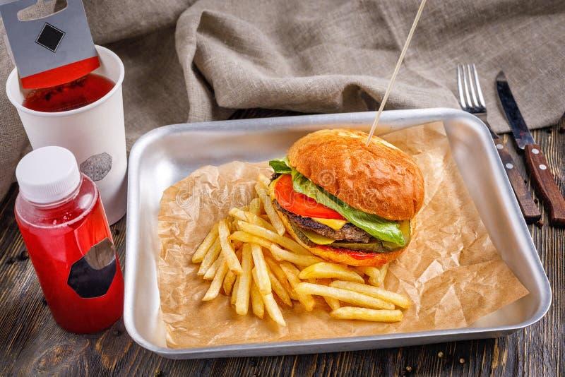 Hamburguesa grande con la chuleta y las verduras de la carne de vaca tres con las patatas fritas curruscantes de oro y la tostada fotos de archivo