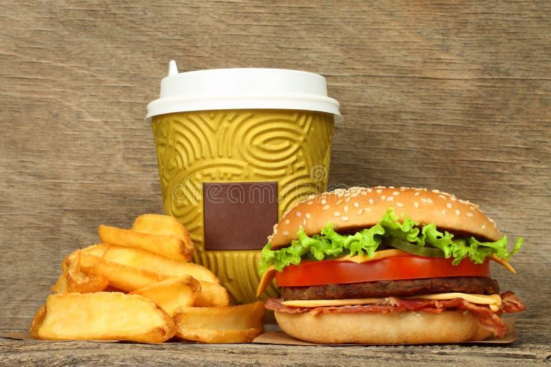 Hamburguesa grande con las patatas fritas y la taza de café del papel fotografía de archivo libre de regalías
