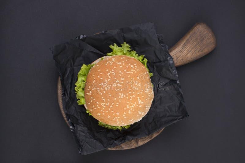 Hamburguesa grande con las semillas de sésamo en un fondo negro Alimentos de preparación rápida y espacio libre para el texto Vis imagenes de archivo