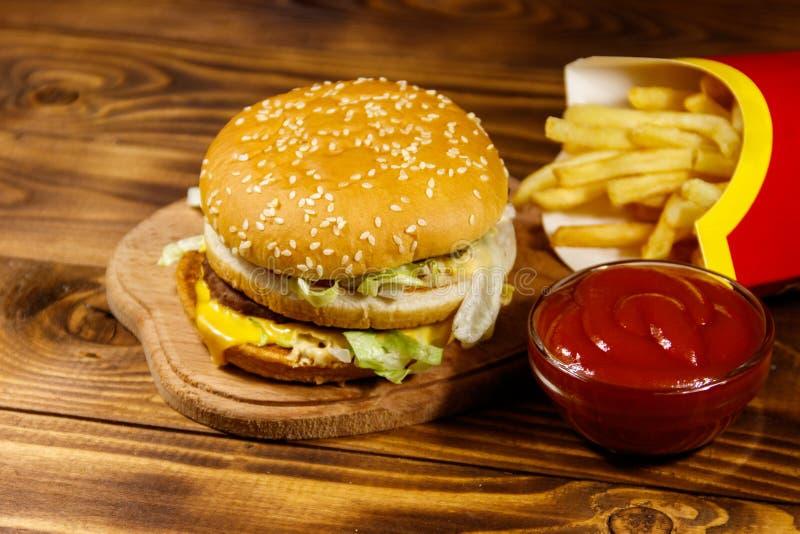 Hamburguesa grande deliciosa con las patatas fritas y la salsa de tomate en la tabla de madera foto de archivo libre de regalías