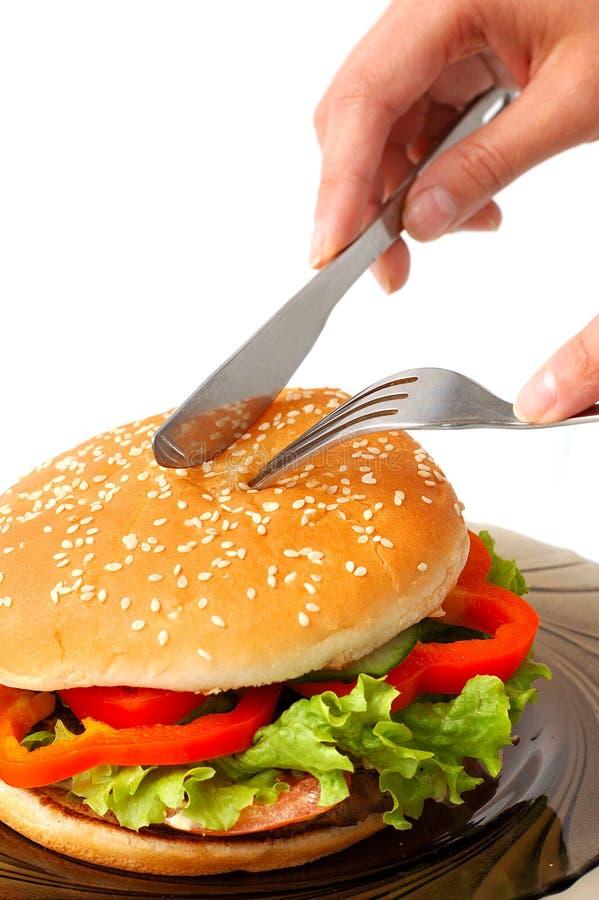 Hamburguesa grande en un rato de la comida de placa imagen de archivo