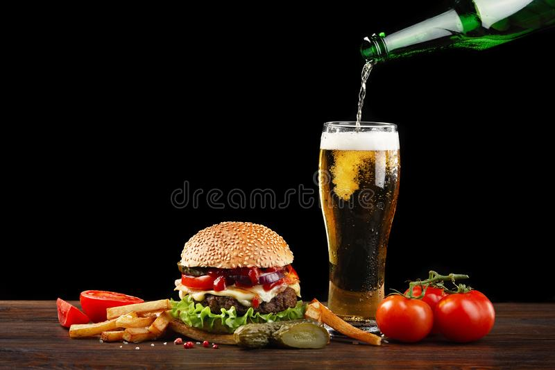 Hamburguesa hecha en casa con las patatas fritas y la botella de cerveza que vierten en un vidrio Comida rápida en fondo oscuro e foto de archivo libre de regalías