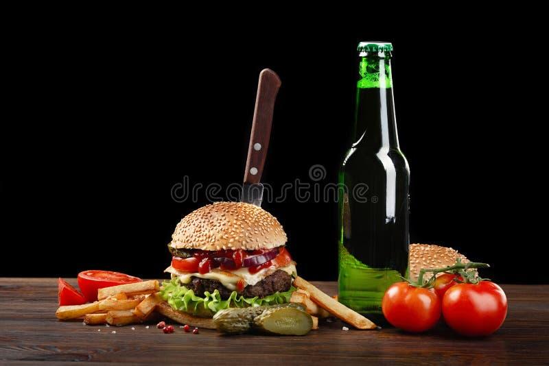 Hamburguesa hecha en casa con las patatas fritas y la botella de cerveza en la tabla de madera En la hamburguesa peg? un cuchillo foto de archivo
