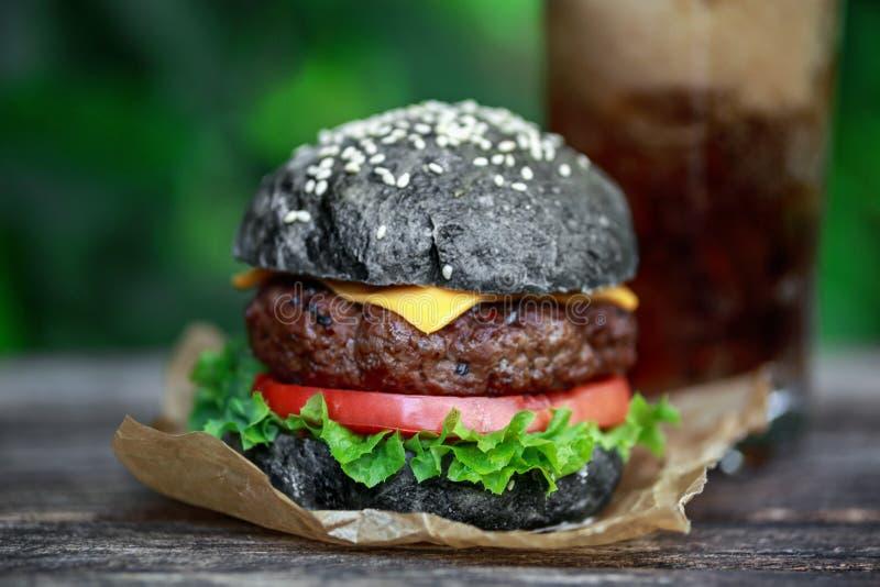 Hamburguesa hecha en casa de la carne de vaca con el bollo, el tomate, la lechuga, el queso y el vidrio negros de limonada fotografía de archivo