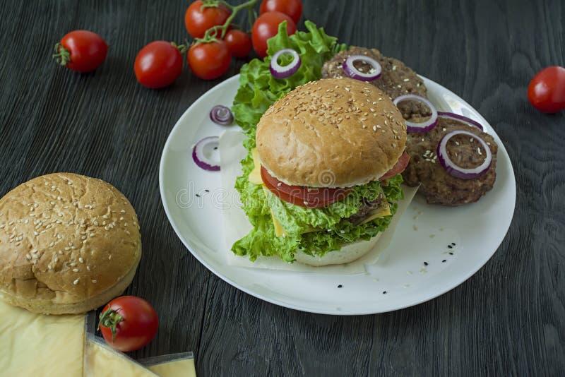 Hamburguesa hecha en casa fresca en una placa blanca Ingredientes para cocinar la hamburguesa Comida malsana foto de archivo libre de regalías