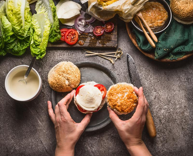 Hamburguesa hecha en casa La mujer femenina da la fabricación de la hamburguesa en fondo de la tabla de cocina con los ingredient foto de archivo