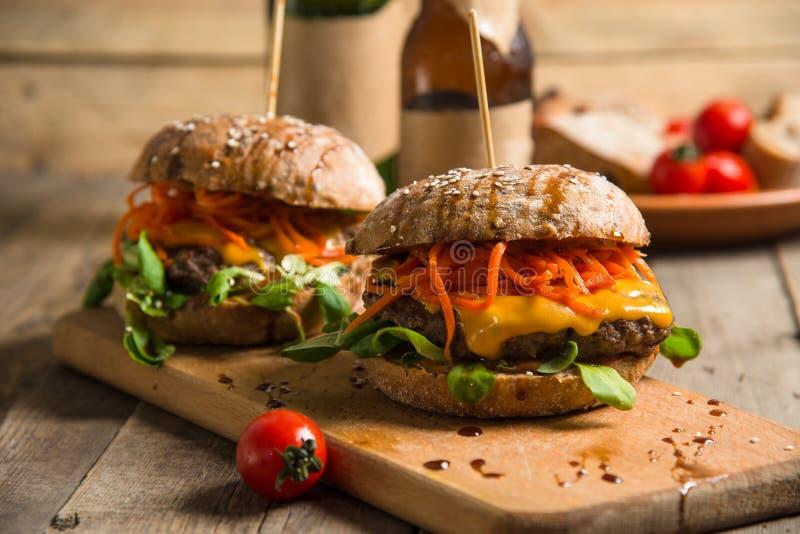 Hamburguesa jugosa con la carne y las verduras en una tabla marrón de madera imagen de archivo