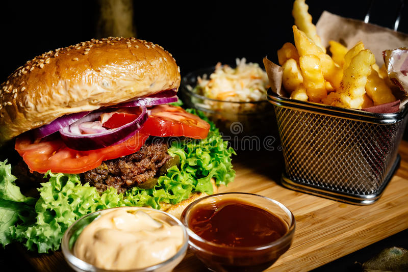 hamburguesa jugosa deliciosa de la carne de vaca, comida americana del estilo con las patatas fritas y ensalada de la ensalada de foto de archivo