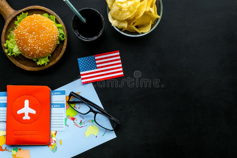 Hamburguesa, mapa, boletos, pasaporte y bandera de los E.E.U.U. para el turismo gastronómico a América en copyspace negro de la o foto de archivo
