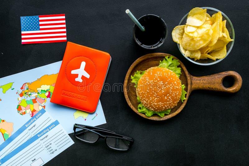Hamburguesa, mapa, boletos, pasaporte y bandera de los E.E.U.U. para el turismo gastronómico a América en la opinión superior del foto de archivo