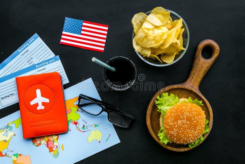 Hamburguesa, mapa, boletos, pasaporte y bandera de los E.E.U.U. para el turismo gastronómico a América en la opinión superior del imagenes de archivo