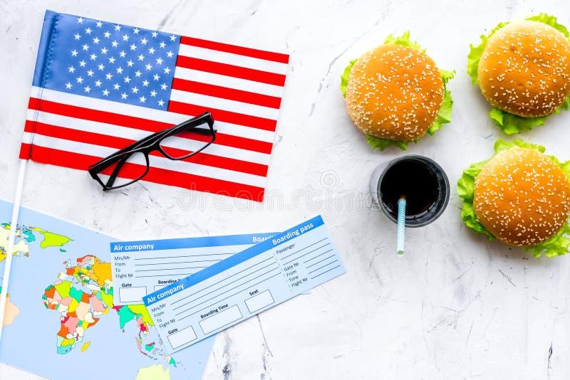 Hamburguesa, mapa, boletos y bandera de los E.E.U.U. para el turismo gastronómico a América en la opinión superior del fondo de m fotos de archivo libres de regalías