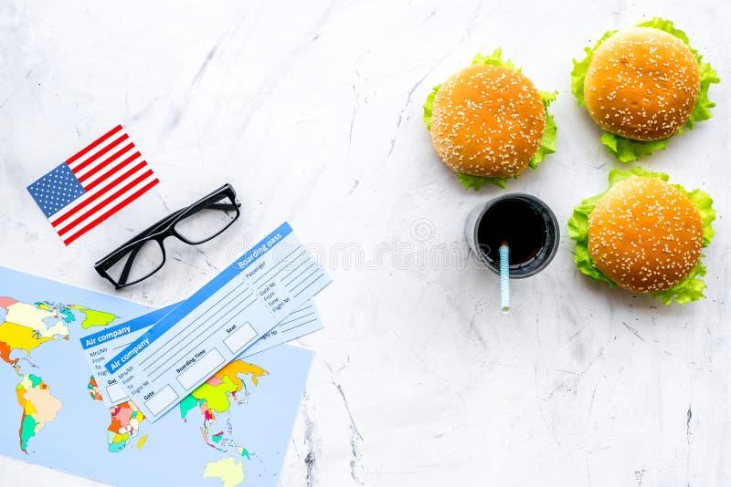 Hamburguesa, mapa, boletos y bandera de los E.E.U.U. para el turismo gastronómico a América en la opinión superior del fondo de m foto de archivo