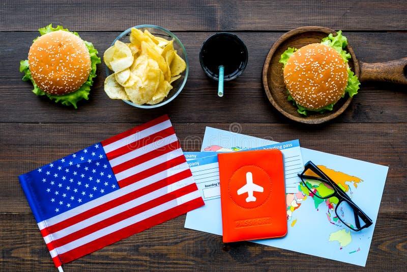 Hamburguesa, microprocesadores, mapa, boletos y bandera de los E.E.U.U. para el turismo gastronómico a América en la opinión supe foto de archivo
